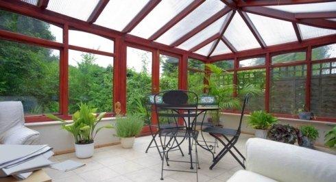 un tavolo con delle sedie, dei divani bianchi in una veranda in pvc bordeaux