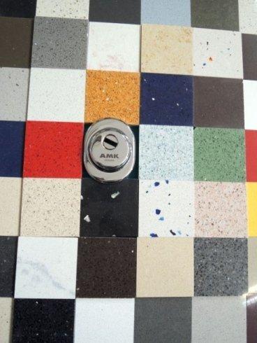 delle piastrelle colorate e al centro una serratura in esposizione