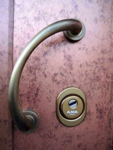 una maniglia in ottone e una serratura di una porta color rosa a sfumature nere