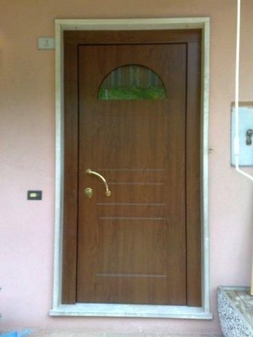 una porta in legno marrone con un piccolo vetro in alto e  una maniglia dorata