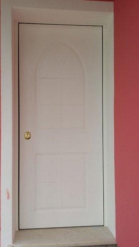 una porta di legno di color bianco con una maniglia dorata