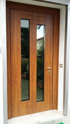 una porta d'entrata in legno e due vetri al centro