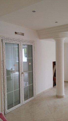 una porta in vetro in una casa e a destra una colonna di marmo