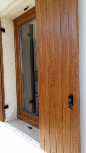 un'anta di una persiana in legno e dietro una finestra