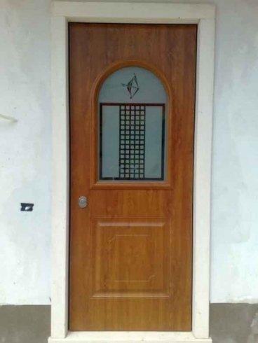 una porta in legno con un vetro a disegni neri al centro