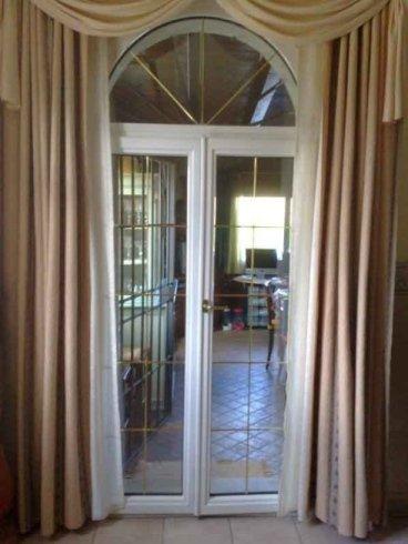 una porta in vetro e sopra delle tende dorate a drappeggio