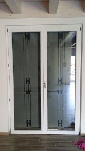 una porta in pvc bianco e vetro  a due ante