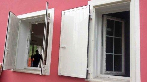 due finestre con delle persiane bianche aperte