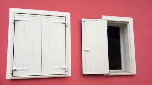 una finestra con le persiane bianche chiuse e una aperta