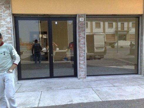 una porta in pvc nero e vetro e una vetrata vicino