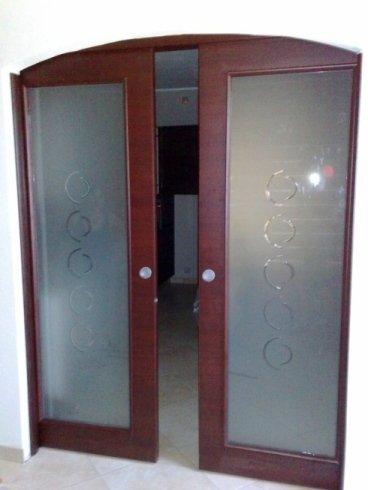 una porta in legno bordeaux e vetro a due ante scorrevoli