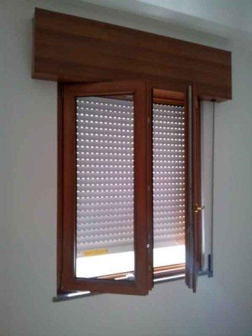 una finestra in legno aperta con una tapparella bianca abbassata