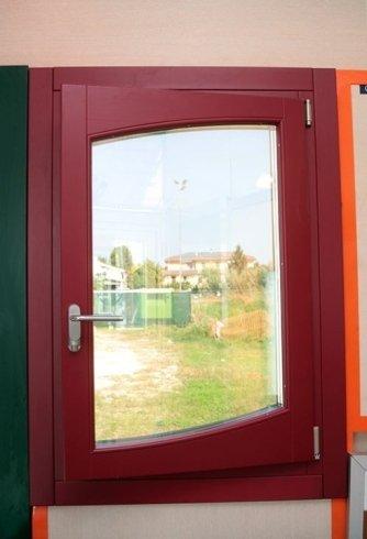 una finestra bordeaux con una maniglia in acciaio e vista dell'esterno