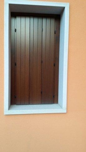 una finestra con le ante delle persiane in legno chiuse