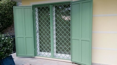 una griglia anti intrusione verde e due ante delle persiane spalancate di color verde
