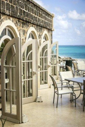 delle porte in legno e vetro color beige aperte, un terrazzo con dei tavoli e vista del mare