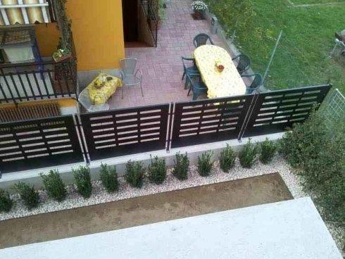 vista dall'alto verso il basso di una ringhiera nera in ferro in un giardino
