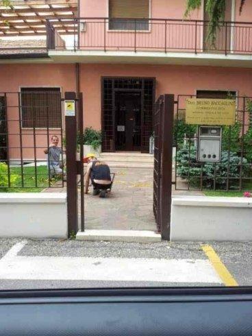 un cancello in ferro bordeaux aperto e vista di un cortile con delle persone