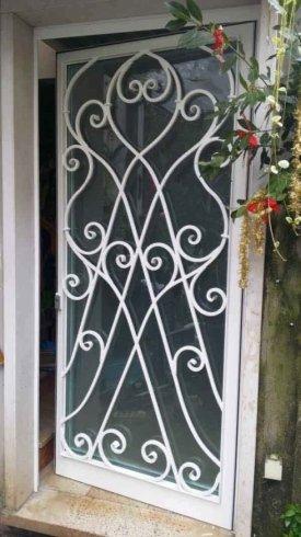 una griglia in ferro di una finestra con ornamenti a forma di spirale