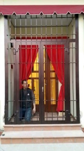 una porta con una griglia in ferro marrone e dietro un uomo