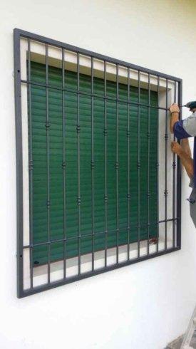una griglia anti intrusione davanti a una finestra con una tapparella verde abbassata