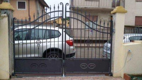un cancello d'entrata e fuori un suv grigio parcheggiato