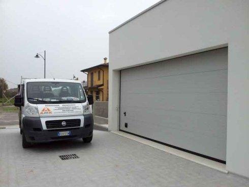 un furgone bianco e accanto una porta d'entrata a un garage