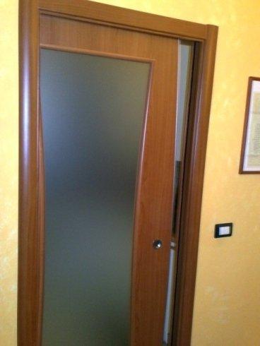una porta in legno e vetro socchiusa