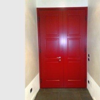 una porta chiusa a due ante in legno di color rosso