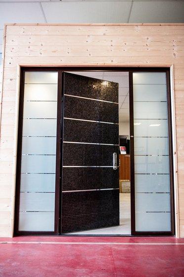 una porta piastrellata di color nero semi aperta e sui lati due vetrate
