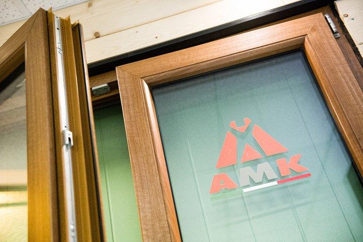 una porta in legno e vetro semi aperta e il logo AMK sul vetro
