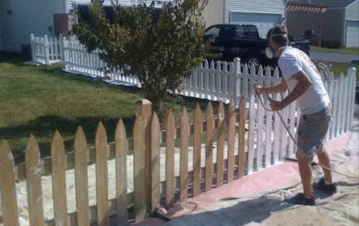 Expert painting the exterior fence