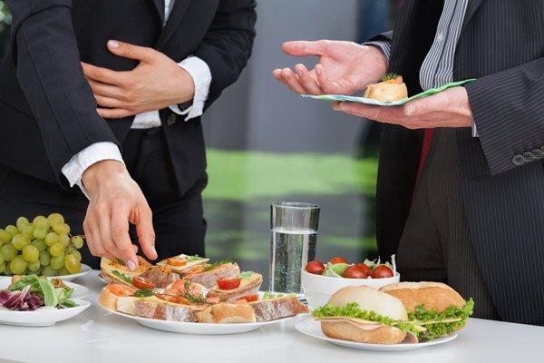 uomini d'affari mentre parlano al pranzo a buffet