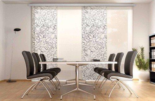 Studio con tavolo e sedie di acciaio e una tenda avvolgente di due colori bianca e stampata bianca e grigia