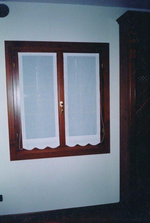 Finestra di legno con due tendine pieghevole bianche