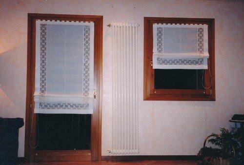 Porta e finestra di legno con le tendine pieghevole bianche