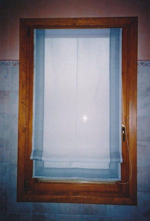 Finestra di legno con tendina pieghevole bianca con banda blu