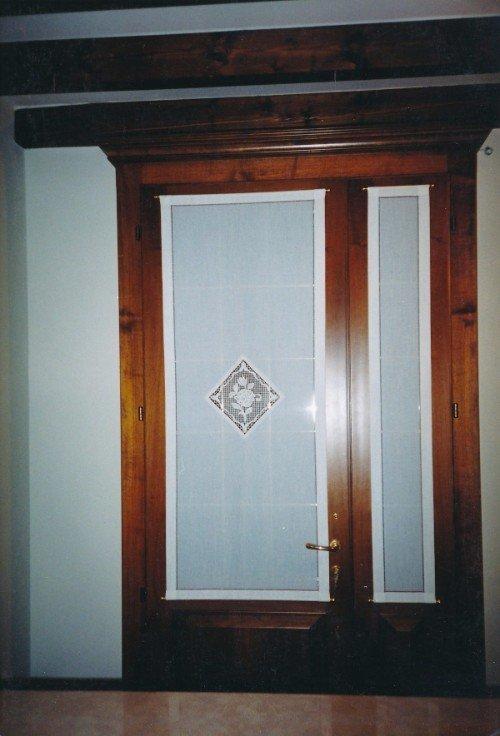 Porta di legno e vetro con tendine bianche