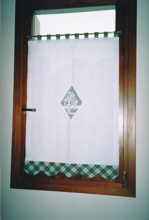 FInestra di legno con tendina bianca con banda verde