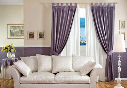 Salon con sofá bianco, parete color malva ,tendine bianche e tende malva