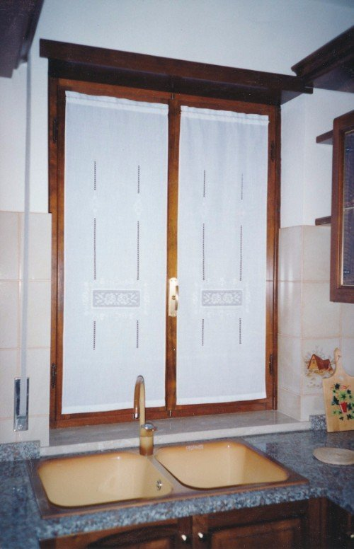 Finestra da cucina con tendine ricamati bianchi