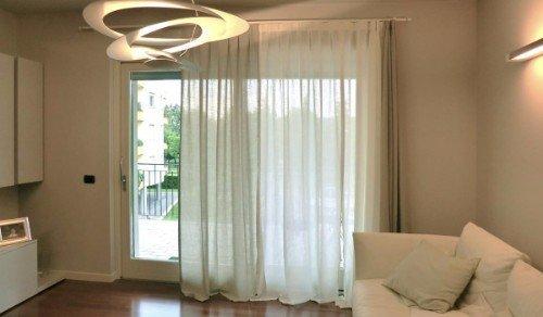 Salon con sofá color crema chiara  e tendine