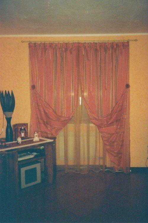 Stanza con parete arancione , tendine chiaro e copre tenda a razze rossa