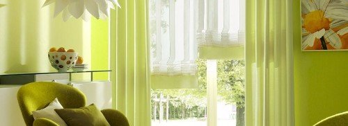 Stanza di colore verde limone con tendine bianche e tende verde chiaro