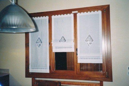 Finestra di legno di tre foglie con tendine bianche ricamate