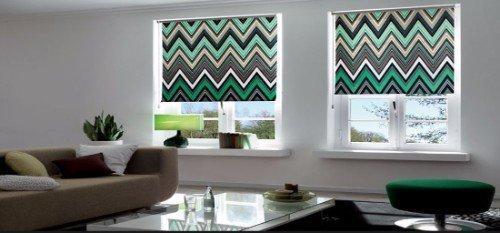 Salon con sofá marrone  e due tendine con disegno zigzag verde e grigio