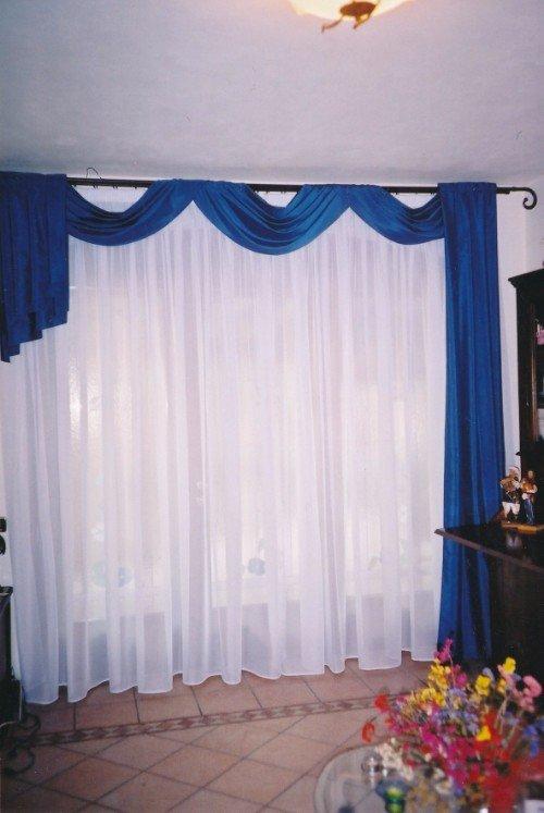 Grande finestra con tendine bianche e copre tende blu