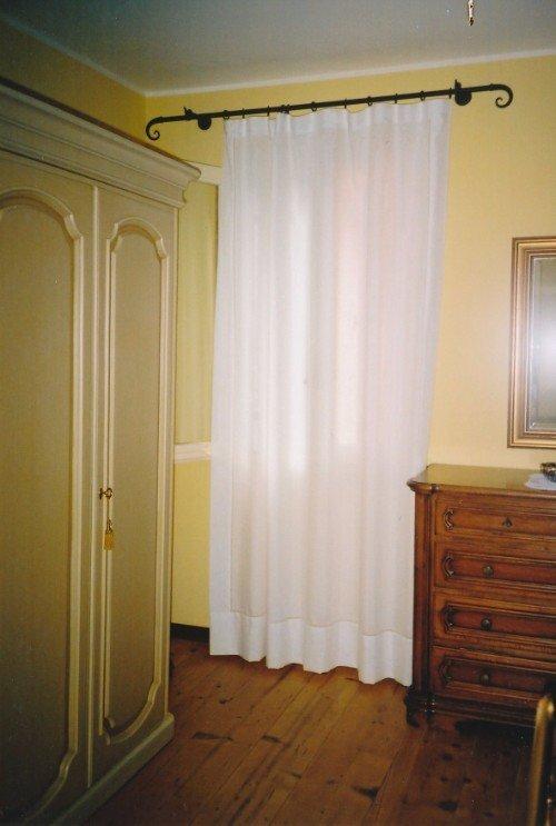Camera con suolo di legno e tendine bianche