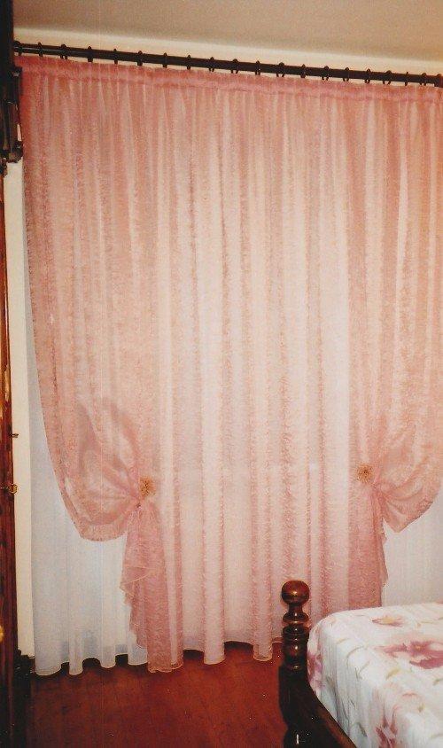 Camera di letto matrimoniale con tendine bianche e copre tende rose
