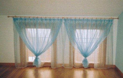 Due grande finestre con tendine bianche e copre tende blu